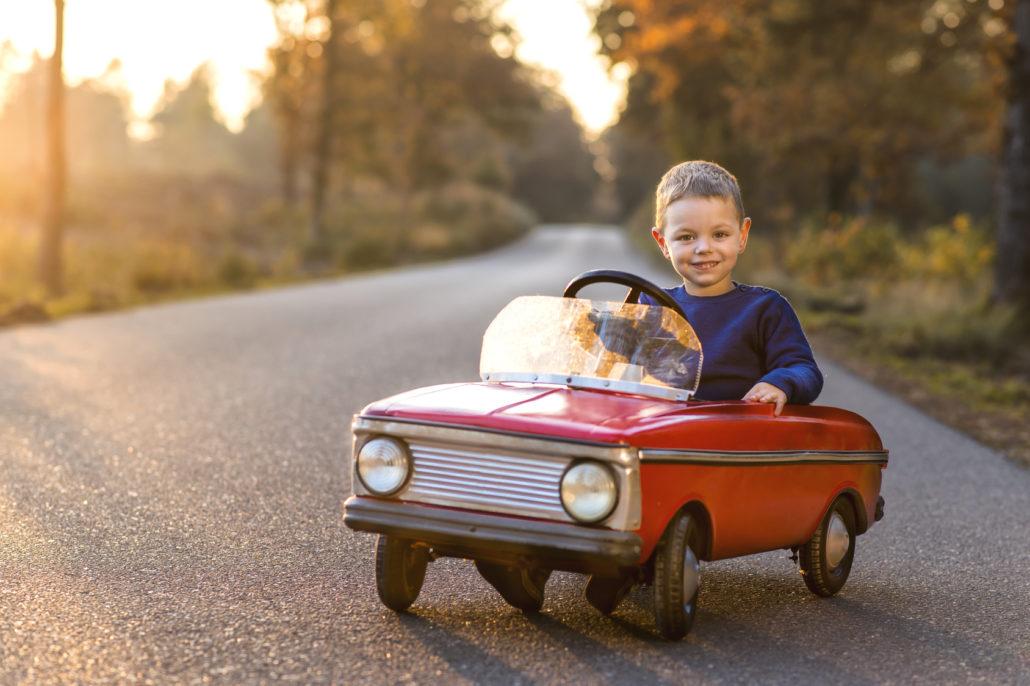 grappig kind in zijn auto onderweg tijdens zonsondergang in de herfst